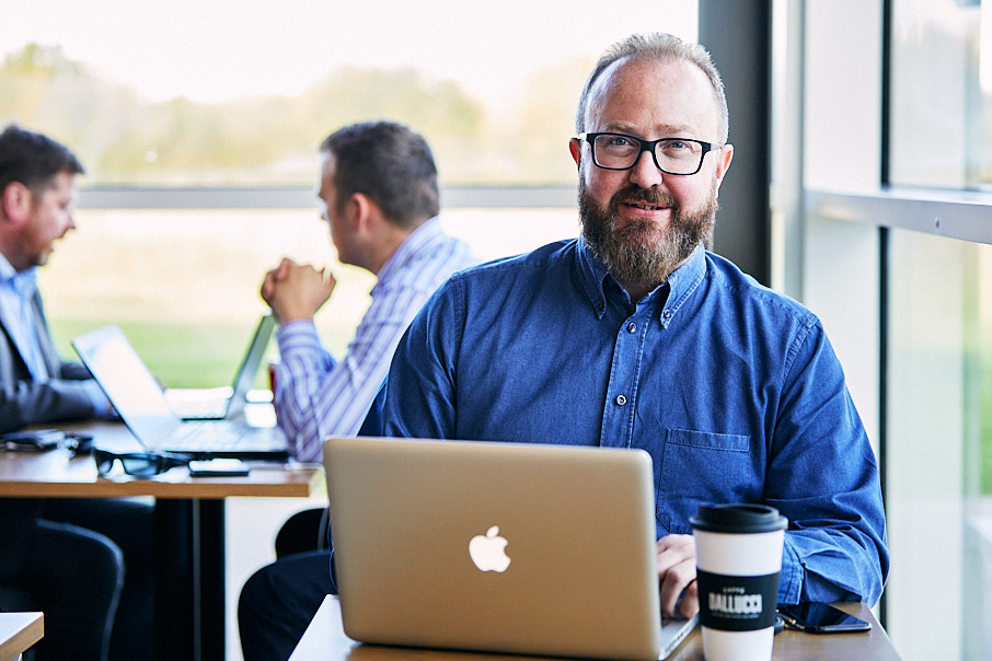 Personal branding photography of man in cafe at laptop