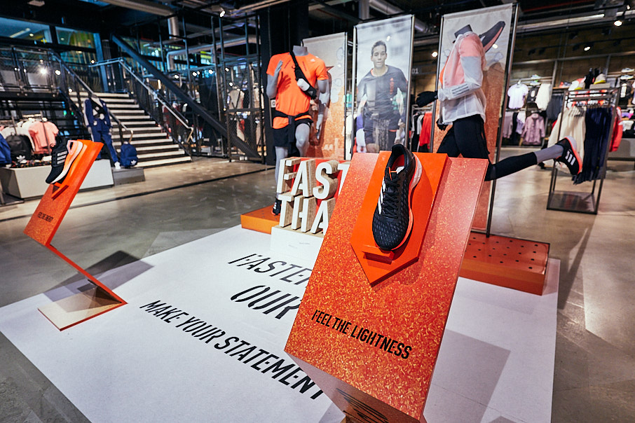 Interior of adidas store with orange and black trainers in view