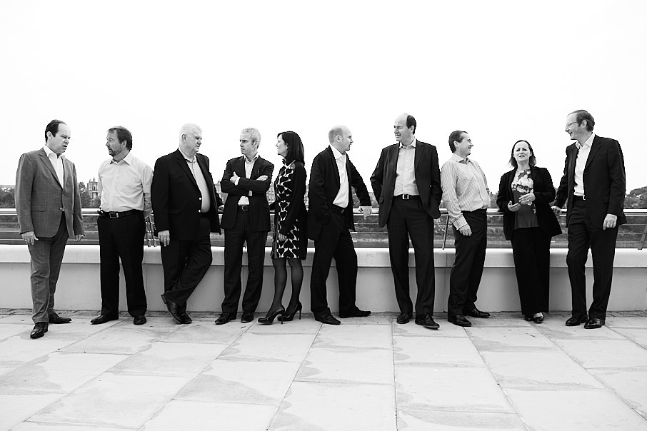 Black and white portrait of a group of company directors lined up looking in different directions