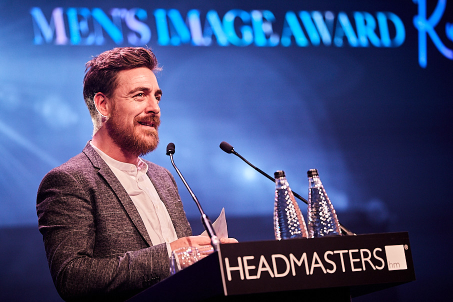 Man presenting an award on stage