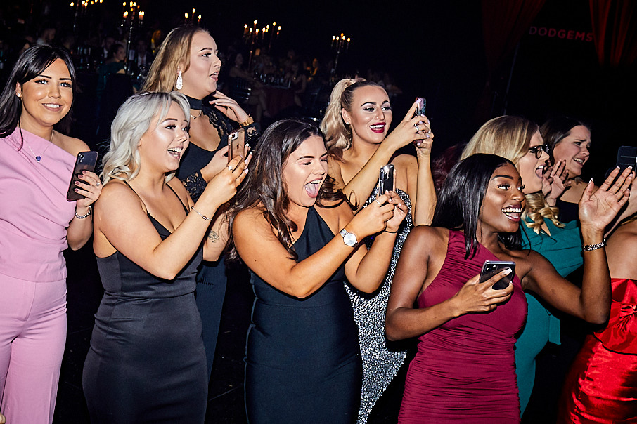 A group of young stylish women laughing and taking photos