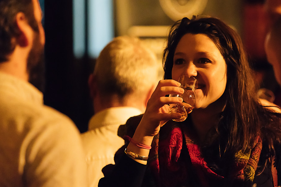 Atmospheric image of woman drinking whisky and smiling to a friend