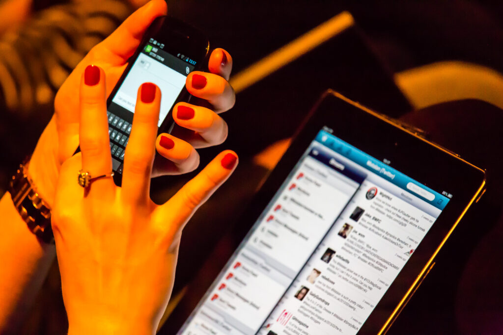 Fingers with red nails typing on a smart phone